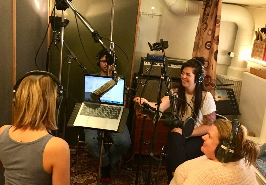 Projektteamets fyra medlemmar i en studio, sitter i ring, skrattar, har mikrofoner framför sig och hörlurar på huvudet.