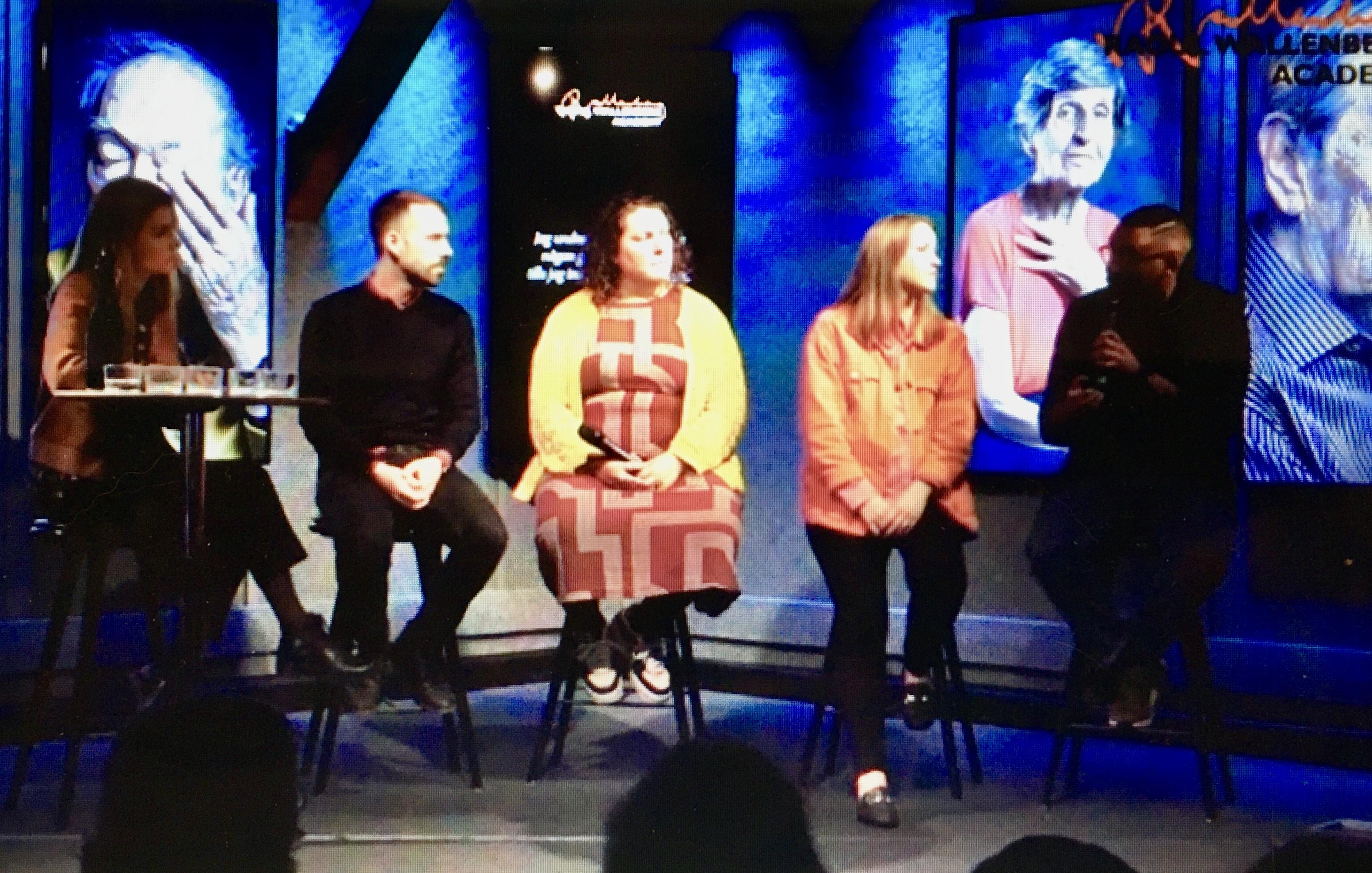 Moderatorn och panelen på rad på mörkblå scen.