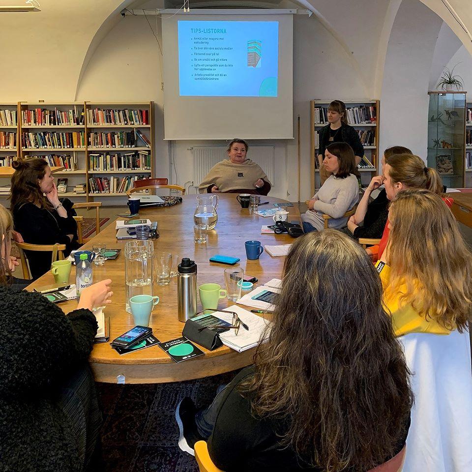 Foto på Maria och Kristina som föreläser. I förgrunden syns människor som sitter runt ett stort runt bord.