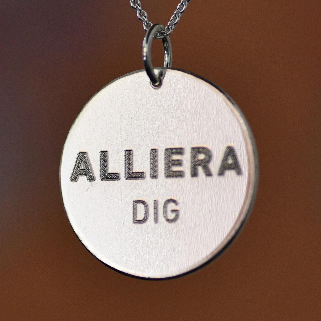 Rund silverplatta med stansad text: Alliera dig