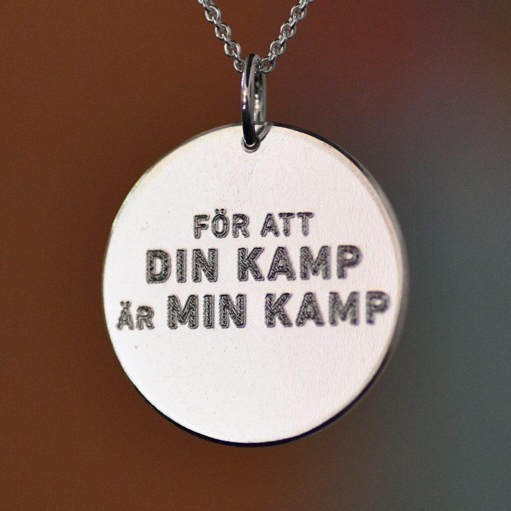 Rund silverplatta med stansad text: För att din kamp är min kamp