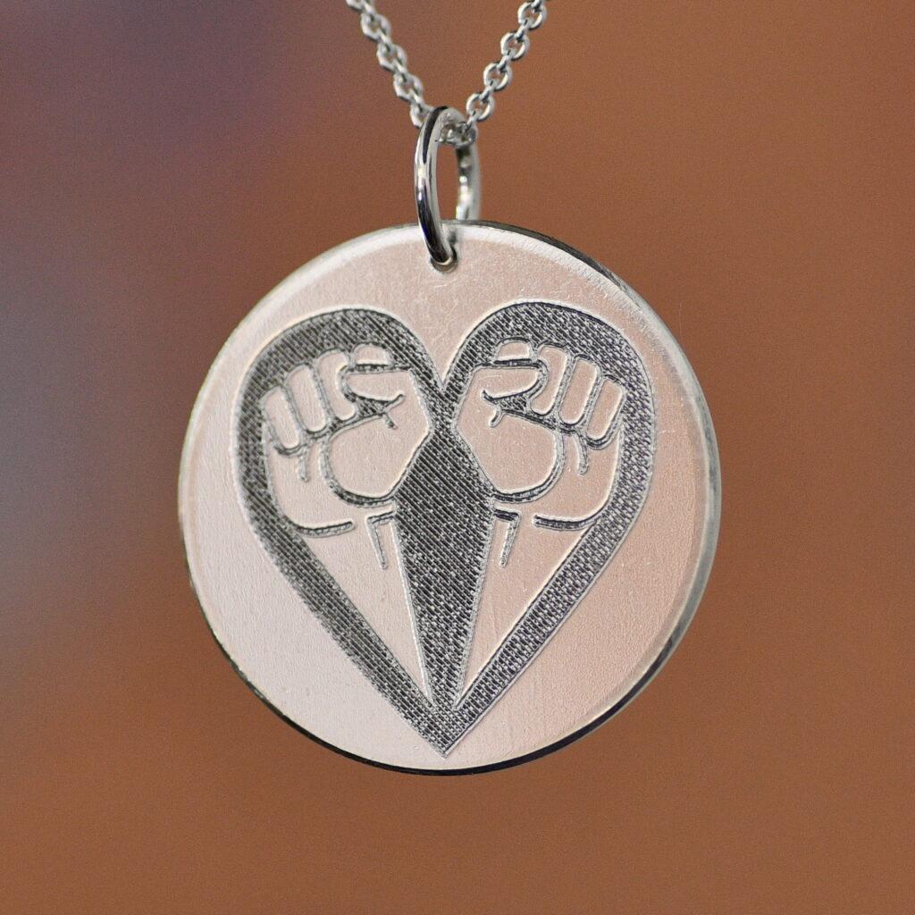Rund silverplatta med utstandsad symbol av två knutna nävar som bildar ett hjärta